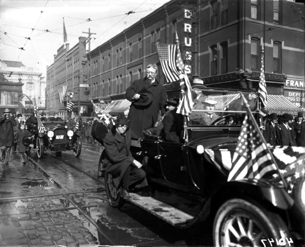 Spectators watch as former President Theodore Roosevelt rides in an open automobile, with Secret Service Agents, in a motorcade down 17th (Seventeenth) Street in Denver, Colorado. Circa 1910. (Harry Mellon Rhoads/Denver Public Library/Western History Collection/Rh-87)  historic; denver public library; dpl; archive; archival; denverite