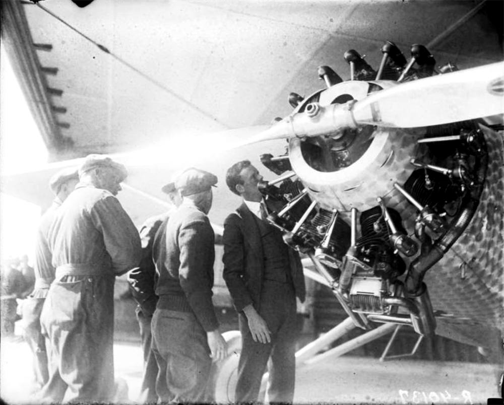 Charles A. Lindbergh inspects the engine of probably a Ryan B-1, manufactured by the B.F. Mahoney Aircraft Corporation, in Denver, Colorado. Between 1920 and 1930. (Harry Mellon Rhoads/Denver Public Library/Western History Collection/Rh-79)  historic; denver public library; dpl; archive; archival; denverite