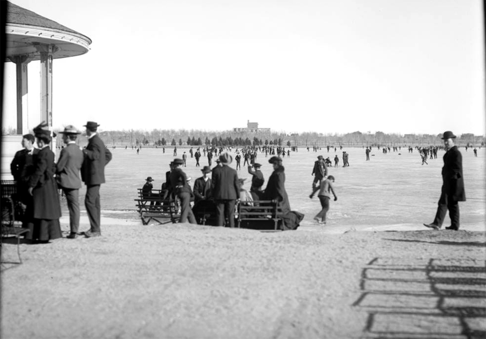 Ice skating on City Park Lake, Denver, Colorado; view east to Museum of Natural History building under construction in 1901; shows edge of City Park bandstand far left and groups seated on park bench on sandy shore. Circa 1901. (Louis Charles McClure/Denver Public Library/Western History Collection/MCC-410)  historic; denver public library; dpl; archive; archival; denverite