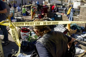 """JR Gerhard ducks under caution tape to collect his belongings. """"Homeless sweeps"""" on Nov. 15, 2016. (Kevin J. Beaty/Denverite)homeless; sweeps; denver rescue mission; police; justice; kevinjbeaty; denver; denverite; colorado; camping ban; right to rest;"""