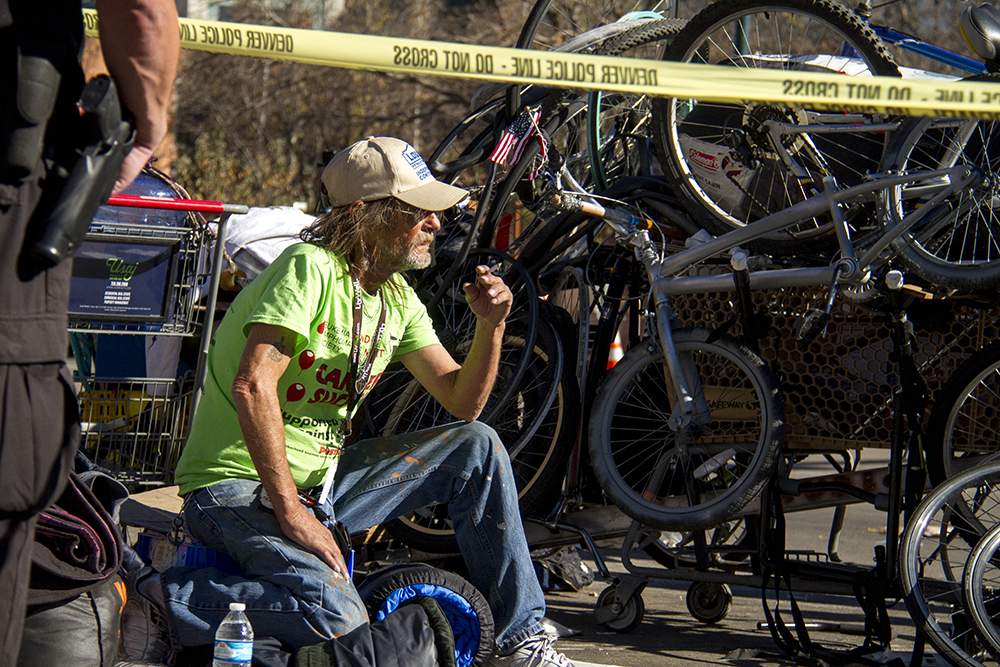 "Randy Russell sits beyond a police line. ""Homeless sweeps"" on Nov. 15, 2016. (Kevin J. Beaty/Denverite)homeless; sweeps; denver rescue mission; police; justice; kevinjbeaty; denver; denverite; colorado; camping ban; right to rest;"