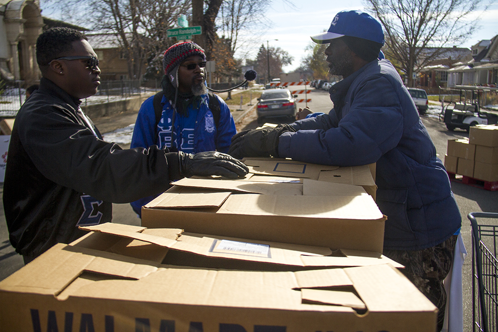 Van McGee (right to left), Mayo Thompson and Terri Nelson stand around boxes of donated food outside of the High Street United Methodist Church. Nov. 11, 2016. (Kevin J. Beaty/Denverite)  High Street United Methodist Church; five points; bruce randolph; thanksgiving; volunteer; charity; community service; kevinjbeaty; denver; denverite; colorado;
