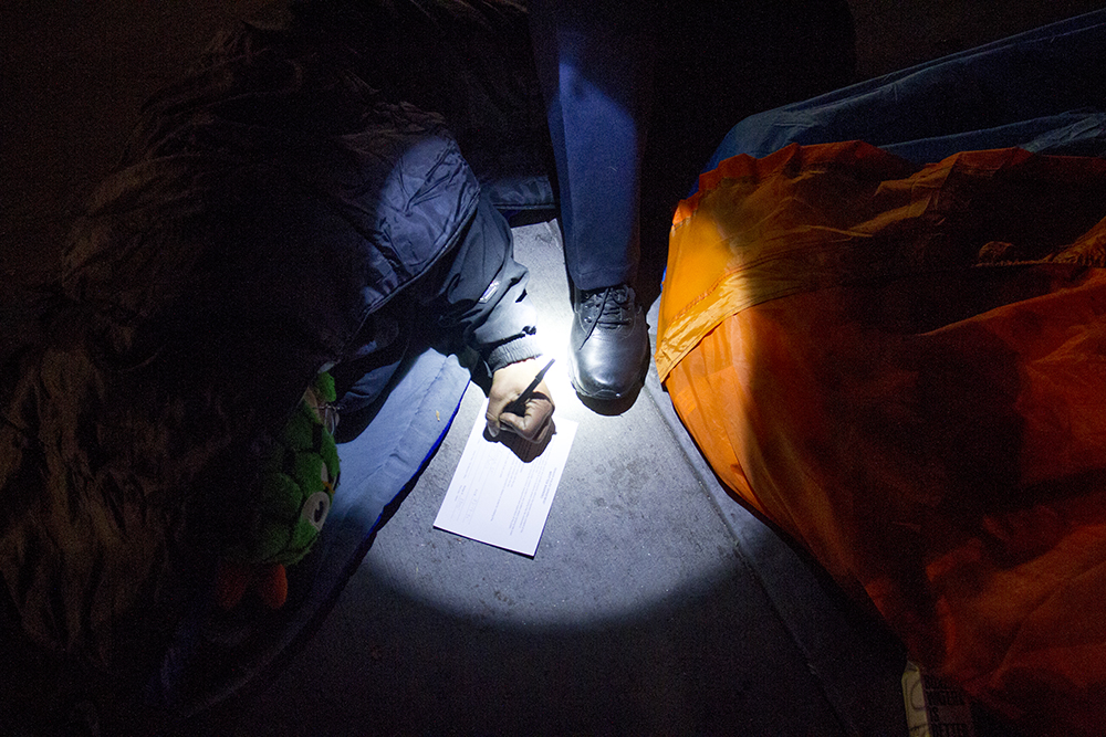 "A man who goes by ""Possum"" signs a written warning to vacate. Protesters who have set up camp in front of the City and County Building to denounce Denver's urban camping ban are removed by police. Nov. 29, 2016. (Kevin J. Beaty/Denverite)  camping ban; right to rest; homeless sweeps; city and county building; police; protest; kevinjbeaty; denver; denverite; colorado;"