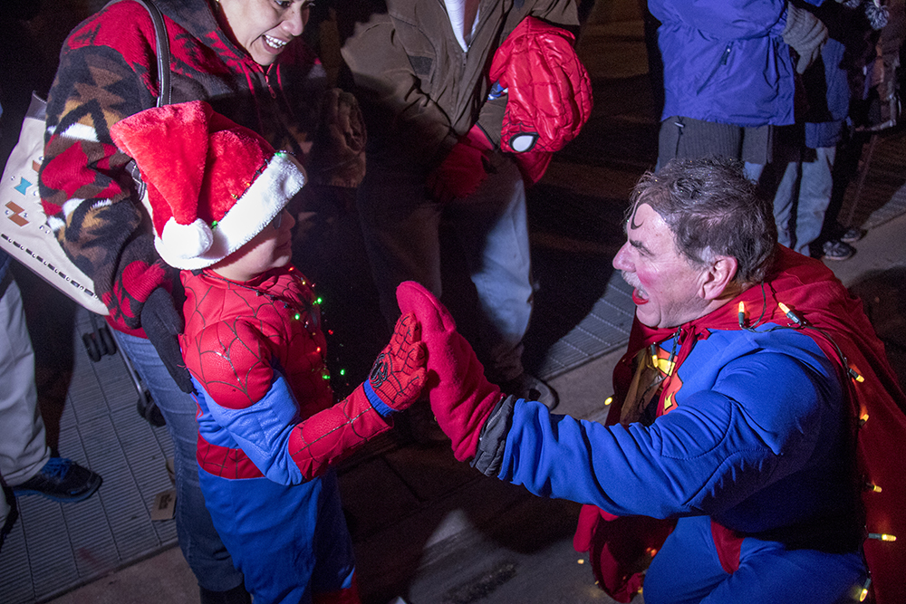 Superman high-fives spiderman. Parade of lights. Dec. 2, 2016. (Kevin J. Beaty/Denverite)
