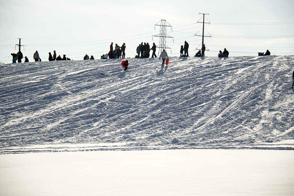Young and old alike gather atop Ruby Hill to fly down it into the snow. Dec. 17, 2016. (Kevin J. Beaty/Denverite)snow day; winter; sledding; denver; denverite; colorado; kevinjbeaty;