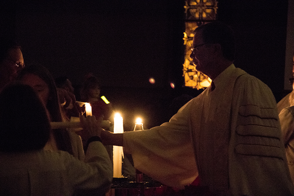 Senior pastor Mike Dent lights candles during the 7 P.M. service. Christmas Eve at Trinity United Methodist Church, 2016. (Kevin J.Beaty/Denverite)  christmas eve; holidays; downtown; kevinjbeaty; denver; denverite; colorado;