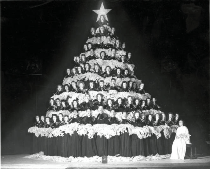 Photograph of the annual singing Christmas Tree at West High School in Denver, Colorado. Eight levels of students stand on a circular platform decorated as a Christmas Tree while singing. Beside the tree a singe female students sits on a stool dressed in white. (Denver Public Library/Western History Collection/WH1990)