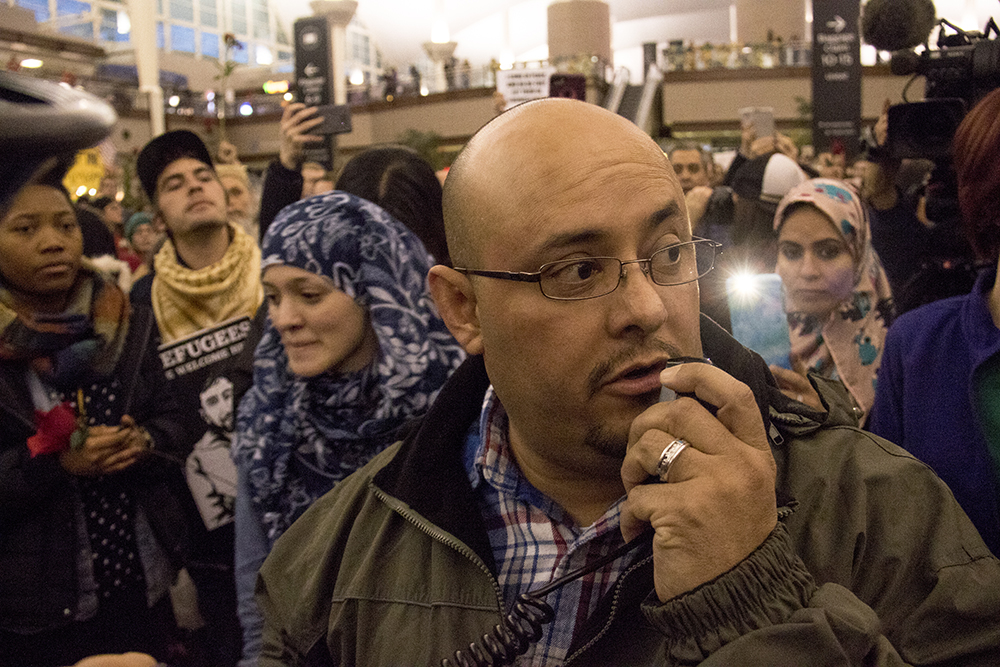 Colorado Representative Joe Salazar tells protesters at DIA that they could be arrested, Jan. 28, 2017. (Kevin J. Beaty/Denverite)  amal kassir; immigration; refugees; politics; protest; copolitics; rally; dia; denver; colorado; kevinjbeaty;