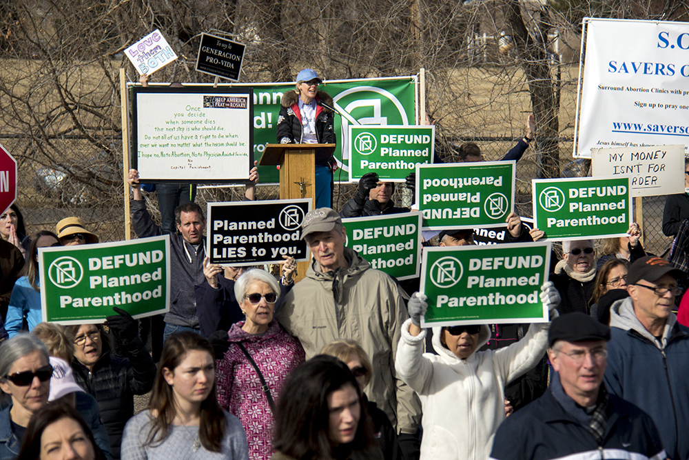 Protesters hold up signs toward Planned Parenthood of the Rockies, Feb. 11, 2017. (Kevin J. Beaty/Denverite)  abortion; pro life; planned parenthood; denver; colorado; kevinjbeaty; denverite; copolitics; politics;
