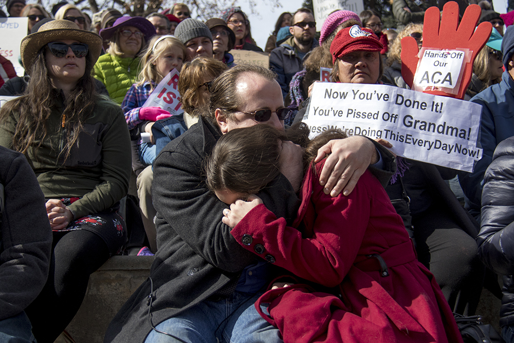 Matthew and Amanda Miller in an emotional embrace after Amanda addressed the crowd about her husband's brush with death. A rally in support of the Affordable Care Act, Feb. 25, 2017. (Kevin J. Beaty/Denverite)  affordable care act; healthcare; aca; copolitics; rally; protest; civic center park; kevinjbeaty; denver; denverite; colorado;