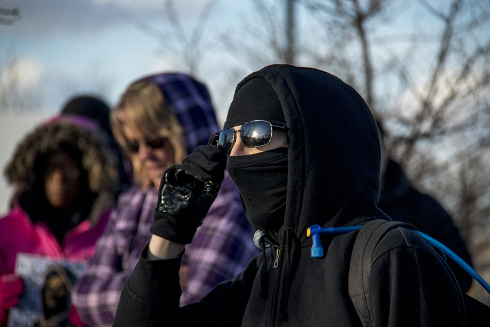 A protester protecting his identity with a mask and sunglasses tells the crowd that they might someday be arrested for attending the rlaly if they do not unify with black clothes and cover their identities. A rally outside of the GEO private immigrant detention facility. (Kevin J. Beaty/Denverite)  ICE; immigration; deportation; aurora; protest; rally; denver; colorado; kevinjbeaty; denverite