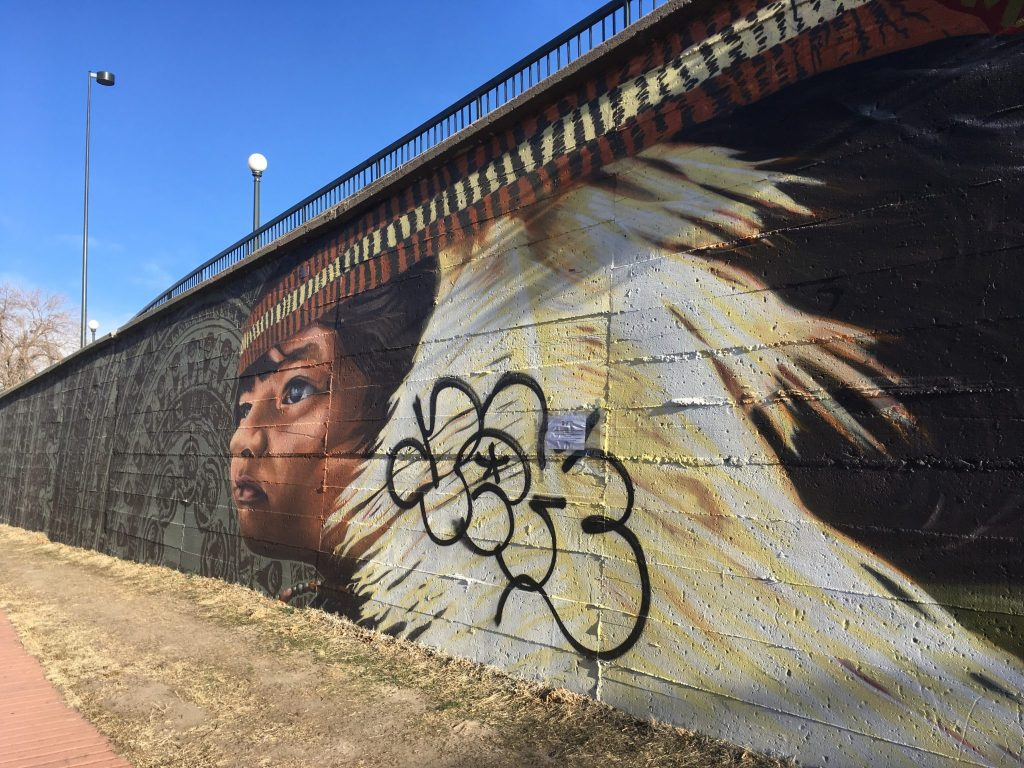 """Vandalism on the """"Paramount"""" murals by Alexandre Orion on the Cherry Creek Trail at Broadway. (Dave Burdick/Denverite)"""