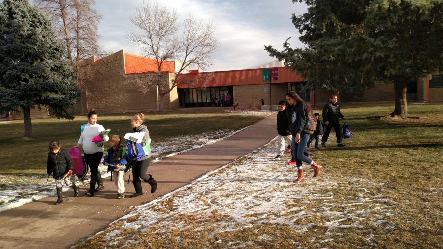 Parents pick up their children at Amesse Elementary, one of two schools that will be restarted. (Eric Gorski/Chalkbeat)