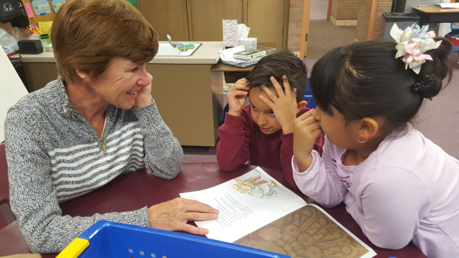 Volunteer Cindy Stechmeyer reads with two second graders during reading club at Lumberg Elementary in Edgewater. (Yesenia Robles/Chalkbeat)