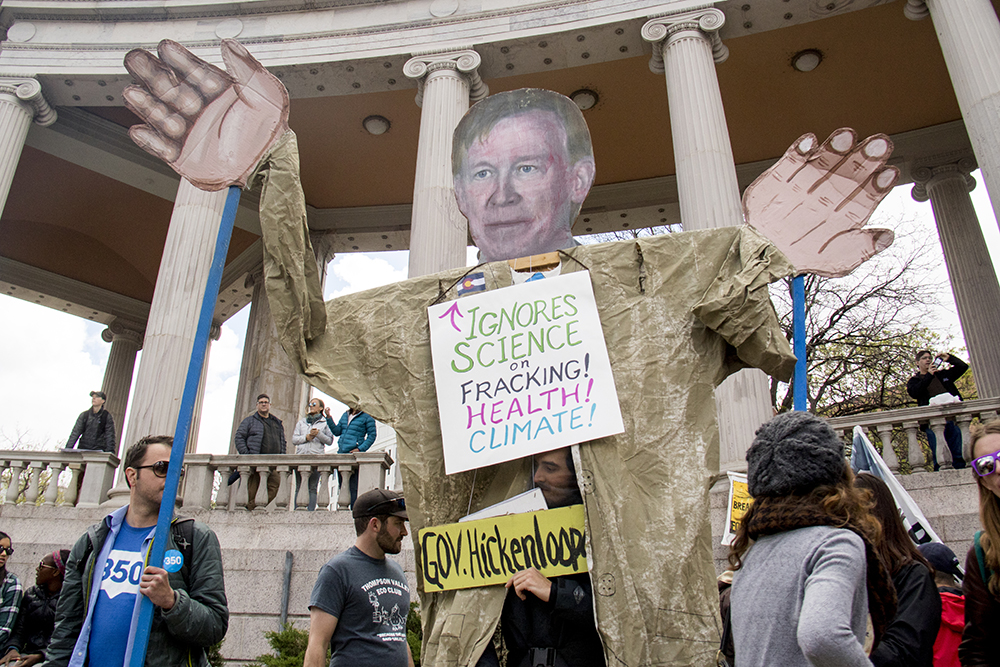 Activists hold up a puppet of Governor John Hickenlooper after interrupting his speech at the March for Science, April 22, 2017. (Kevin J. Beaty/Denverite)  march for science; civic center park; protest; denver; colorado; denverite; kevinjbeaty;