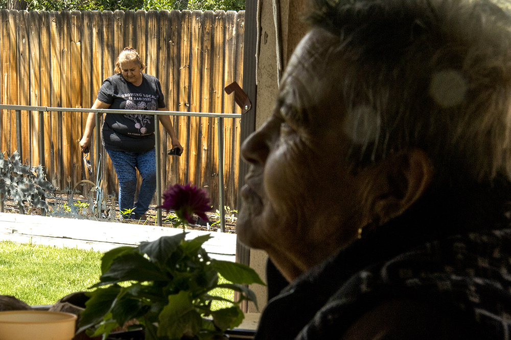 Re:Vision promotora Leticia Manquera works in the garden behind Antonia Aguirre Muñoz's home in Harvey Park, May 26, 2017. (Kevin J. Beaty/Denverite)  food desert; agriculture; gardening; re:vision; revision; harvey park; denver; denverite; colorado; kevinjbeaty;