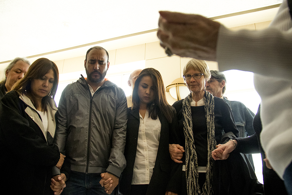 Ingrid Encalada Latorre holds hands with Arturo Hernandez Garcia, surrounded by supporters during a prayer at the Jefferson County courthouse, May 3, 2017. (Kevin J. Beaty/Denverite)  immigration; undocumented; deportation; law; court; jefferson county; golden; colorado; kevinjbeaty