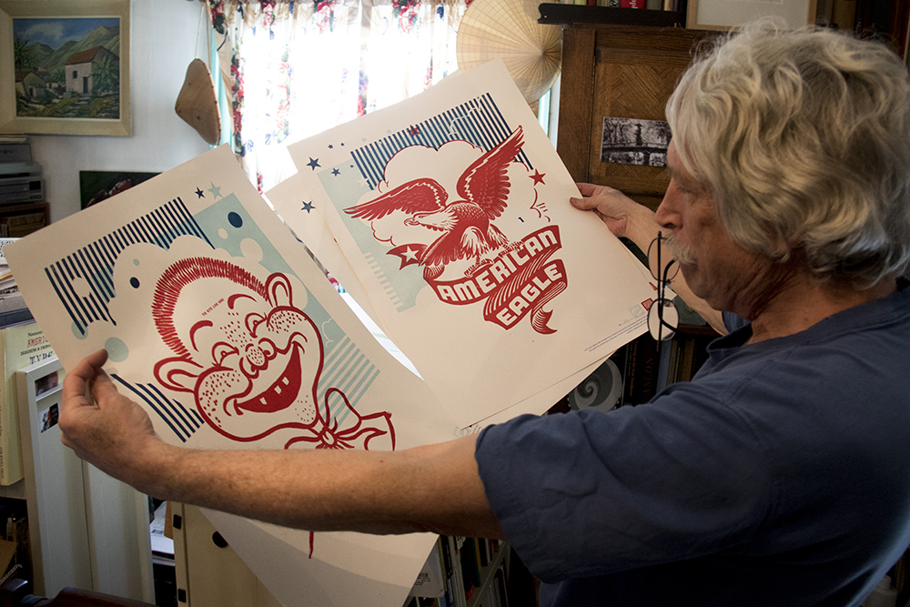 Tom Parson holds up posters that are perks in the Letterpress Depot crowdfunding campaign, May 4, 2017. (Kevin J. Beaty/Denverite)  letterpress; art; englewood; depot; tom parson; collector; kevinjbeaty; denverite; odd spot; denver; colorado;