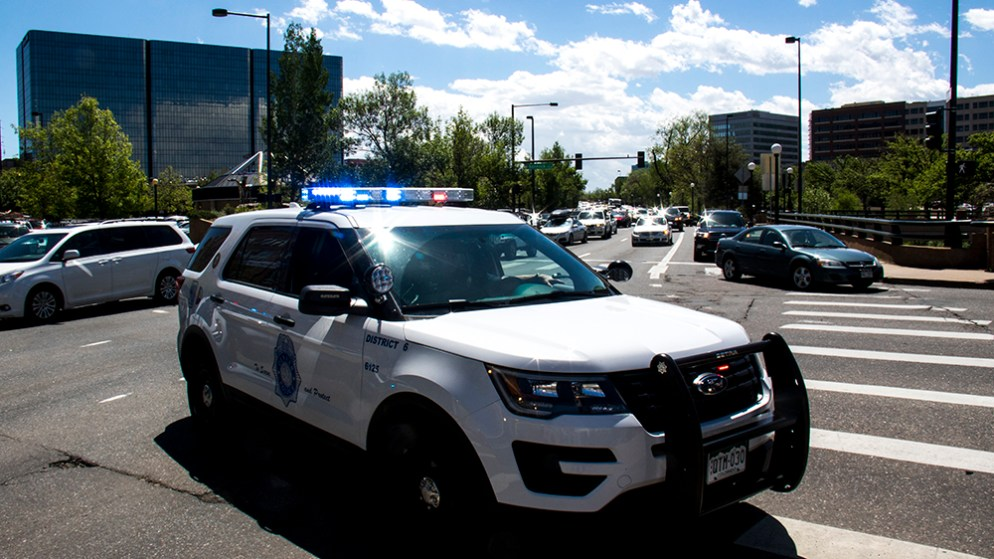 DPD cruisers blocking the intersection of Speer Boulevard and 8th Avenue. (Kevin J. Beaty/Denverite)
