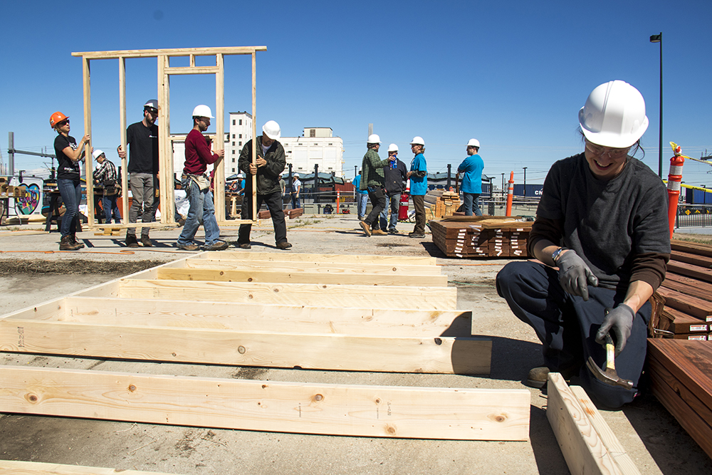 Josh Zeiter hammers a nail. Construction on the Beloved Community Village begins at Walnut and 38th streets, May 20, 2017. (Kevin J. Beaty/Denverite)  homeless; right to rest; tiny home village; rino; five points; denver; denverite; colorado; kevinjbeaty;