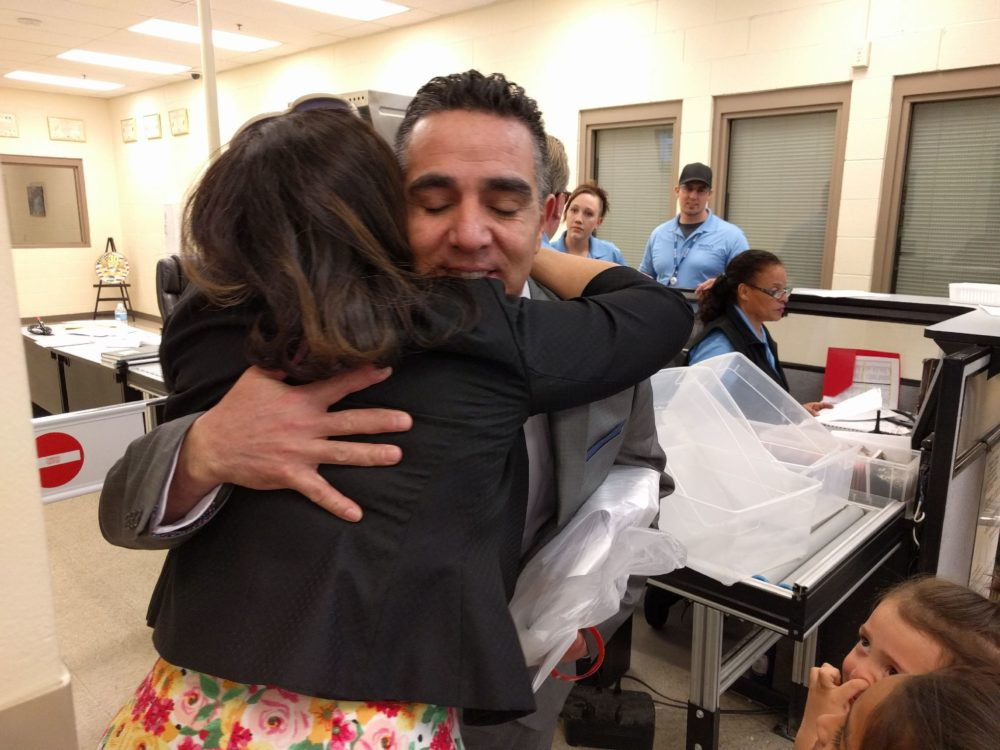 Isidro Quintana hugs his wife, Erica Rodriguez, after learning he'll be able to stay in the United States. (Kevin J. Beaty/Denverite)