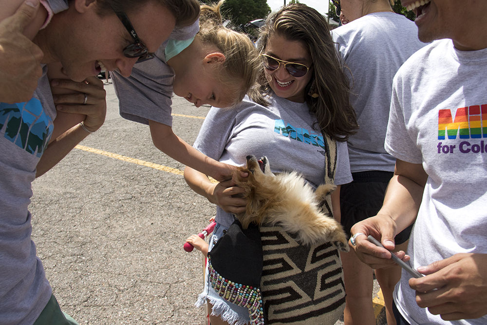 Gubernatorial candidate Mike Johnston says hi to in-bag dog Suki alongside Katherine Marulanda and Darrick Barnes. The Juneteenth parade in Five Points, June 17, 2017. (Kevin J. Beaty/Denverite)
