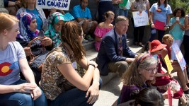Governor John Hickenlooper sits with refgees and allies before speaking on the Capitol steps. World Refugee Day, June 20, 2017. (Kevin J. Beaty/Denverite)  denver; denverite; world refugee day; colorado; kevinjbeaty; capitol hill; rally;