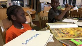 """Greenwood students Ja'zione and Arinze practice spelling the word """"possessions"""" at the Each One Teach One literacy program. (Marissa Page/Chalkbeat)"""