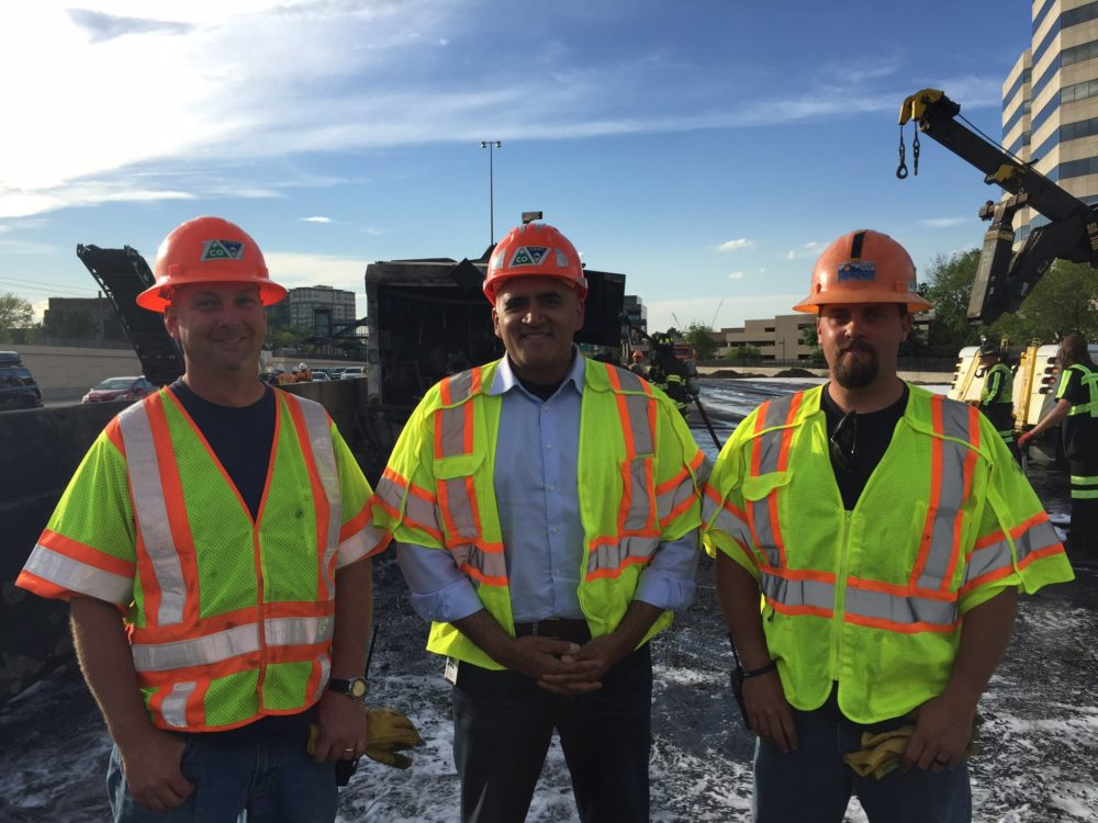 CDOT Executive Director Shailen Bhatt stands at center with two CDOT employees, whose names were not immediately disclosed, who helped a man from a burning fuel truck on I-25. (CDOT)