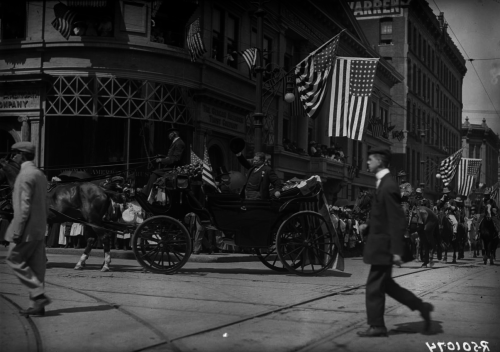 President Theodore Roosevelt waves to spectators as his carriage turns the corner at 17th and Lawrence Streets in an undated photo. Mayor Robert W. Speer is in the carriage. (Harry Mellon Rhoads/Western History & Genealogy Dept./Denver Public Library)