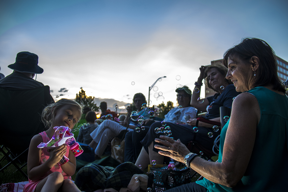 4-year-old Lia blows bubbles with her Noni (Italian for grandmother). The Glendale 4th of July fireworks show, July 1, 2017. (Kevin J. Beaty/Denverite)  denver; colorado; kevinjbeaty; denverite; fourth of july; 4th of july; july 4th; july fourth; independence day; glendale; fireworks