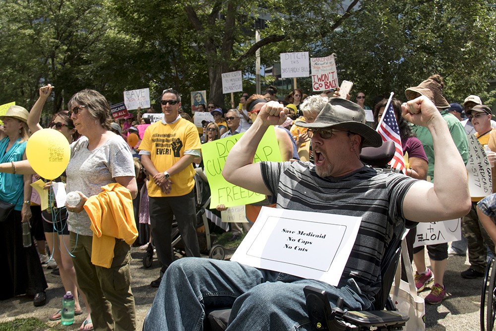 Douglas Howey cheers from his wheelchair. A protest against a Republican Healthcare bill at Skyline Park, July 6, 2017. (Kevin J. Beaty/Denverite)  healthcare; copolitics; politics; adapt; protest; skyline park; denverite; colorado; kevinjbeaty;