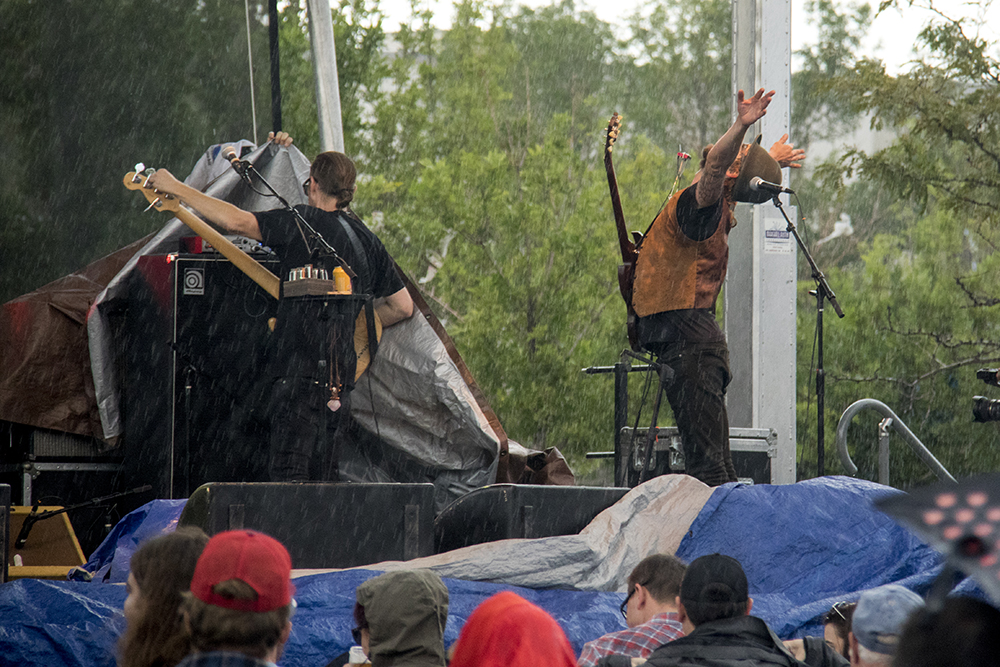 An afternoon drizzles breaks into a full-on deluge at the Underground Music Showcase's main stage, July 31, 2017. (Kevin J. Beaty/Denverite)