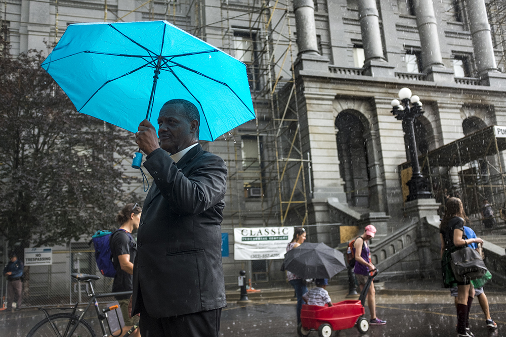 Rev. Timothy Tyler stands under an umbrella as rain-soaked marchers make their way to the Capitol steps. A rally in response to white supremacist protests in Charlottesville, VA, Aug. 13, 2017. (Kevin J. Beaty/Denverite)  protest; charlottesville; rally; denver; colorado; kevinjbeaty; denverite; capitol