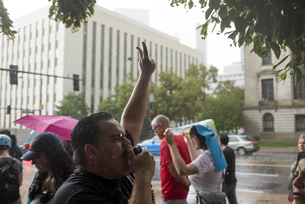 Immigration activist Victor Galvan yells through a bullhorn as drenched protesters make their way to the Capitol steps. A rally in response to white supremacist protests in Charlottesville, VA, Aug. 13, 2017. (Kevin J. Beaty/Denverite)  protest; charlottesville; rally; denver; colorado; kevinjbeaty; denverite; capitol