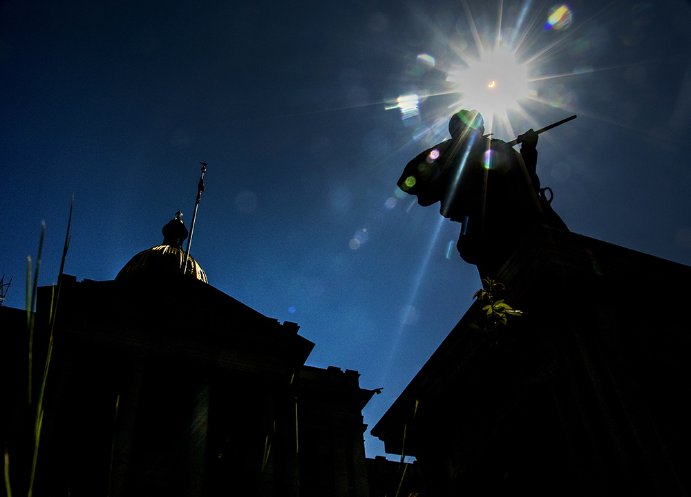 A solar eclipse over the Capitol and a statue dedicated to the Sand Creek Massacre, Aug. 21, 2017. (Kevin J. Beaty/Denverite)  solar eclipse; capitol hill; denver; colorado; the sun; kevinjbeaty; denverite;