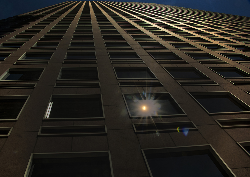 "A solar eclipse seen reflected in the ""cash register building,"" Aug. 21, 2017. (Kevin J. Beaty/Denverite)  solar eclipse; capitol hill; denver; colorado; the sun; kevinjbeaty; denverite;"