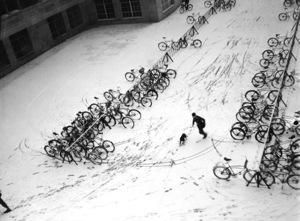 Photograph of the East Denver High School bike rack. Snow covers the ground with several bikes parked on the racks. A male student and a dog can be seen in the middle of the picture. (Denver Public Library/Western History Collection/WH1095)  high school; denver public library; dpl; archive; history;
