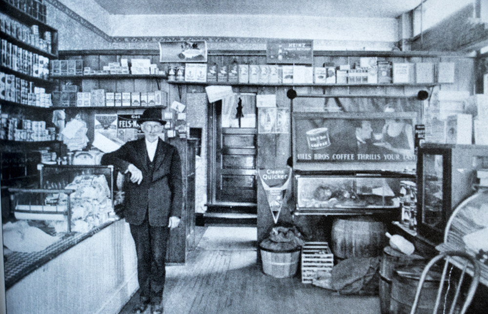 "Label Ginsburg in his grocery store on Grove Street in Denver's west-side Colfax Jewish community, circa 1925. ""When a sign painter made a mistake and spelled the Ginsburg surname with a ""u"" instead of an ""e,"" Label changed the family name."" -Jeanne Abrams, ""Jewish Denver 1859-1940"" (Courtesy: Beck Archives special collection/University of Denver)  judaism; denver; denverite; colorado; religion; history; archival;"