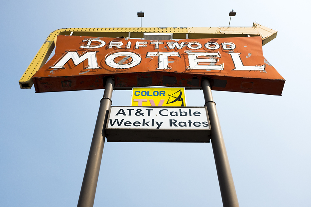 A sign pointing across East Colfax Avenue to the Driftwood Motel on Oneida Street, Sept. 7. 2017. (Kevin J. Beaty/Denverite)  denver; colorado; denverite; colfax; kevinjbeaty; motel; neon;