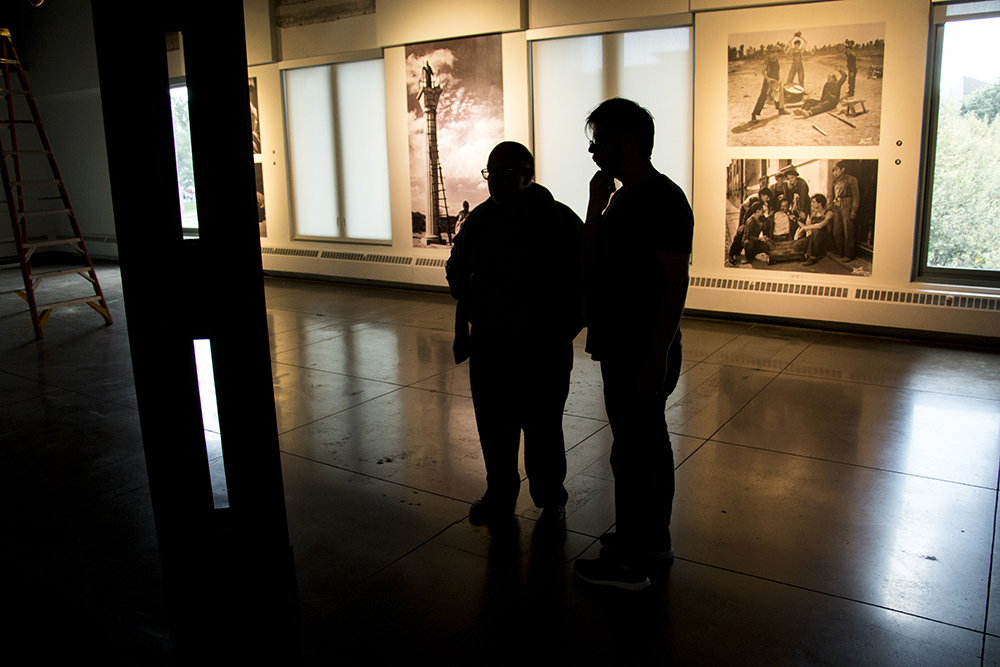 """Alfonso Morales (left) and Héctor Orozco, curators of """"Under the Mexican Sky,"""" an exhibit on the work of cinematographer Gabriel Figueroa at the McNichols Building and part of the Biennial of the Americas. Sept. 12, 2017. (Kevin J. Beaty/Denverite)  mcnichols building; art; biennial of the americas; denver; colorado; denverite; kevinjbeaty;"""