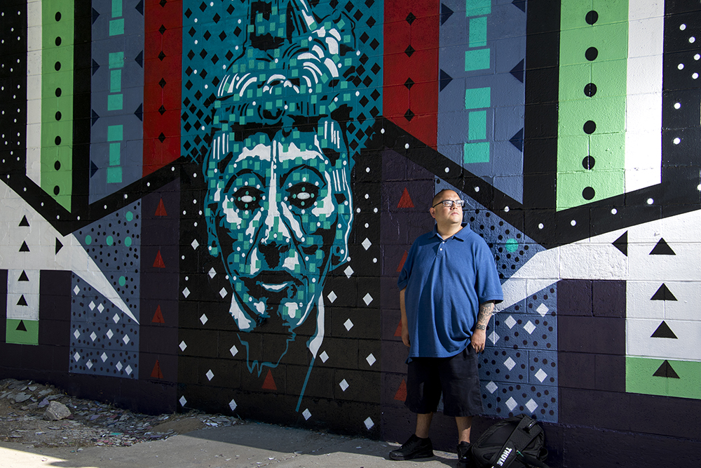 Josiah Lopez and his new mural on the side of Ernie's Auto on Morrison Road, Sept. 12, 2017. (Kevin J. Beaty/Denverite)  denver; colorado; denverite; kevinjbeaty; public art; mural; morrison road; westwood;