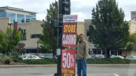 """A man holds a """"store closing sign"""" for the Safeway in Cherry Creek. (Kevin J. Beaty/Denverite)  safeway; cherry creek; kevinjbeaty; colorado; denver; denverite;"""
