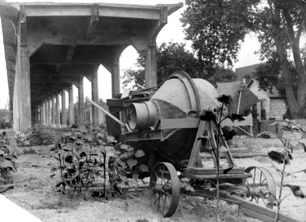 View of a cement mixer and the West Colfax Viaduct during a delay in construction in Denver, Colorado. Sunflowers grow near the machinery. Circa 1915. (Denver Public Library/Western History Collection/X-22600)  colfax; viaduct; archival; history; denver; colorado;