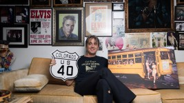 Jonny Barber, lay historian of Colfax historian and former Elvis impersonator, poses with a U.S. 40 sign and a print showing the last day of trolley operation on Colfax Avenue. (Austin Cope/For Denverite) jonny barber; colfax; memorabilia; trolley; colfax museum; U.S. 40