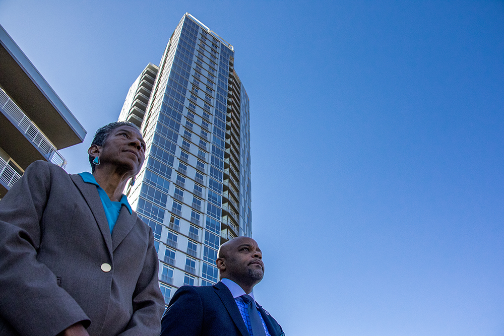 "Denver Parks & Recreation manager Allegra ""Happy"" Haynes and Mayor Michael Hancock stand beneath The Confluence apartment tower while a press conference announced the near-end of Shoemaker Plaza's construction at Confluence Park, Oct. 12, 2017. (Kevin J. Beaty/Denverite)  confluence park; development; denver; colorado; kevinjbeaty; denverite; shoemaker plaza;"