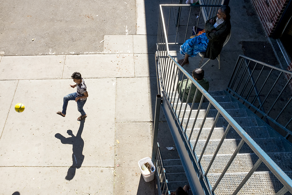 A young man kicks a ball as an elder man watches from above. An apartment building that's home to many of Denver's Burmese refugees, Oct. 15, 2017. (Kevin J. Beaty/Denverite)  aurora; refugee; burmese; myanmar; burma; kevinjbeaty; colorado; denverite; kids; games; rohingya