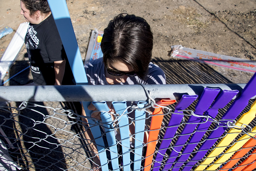 Amanda Kriss slides colored slats into a fence outside the Beloved Community Tiny Home Village, Oct. 29, 2017. (Kevin J. Beaty/Denverite)