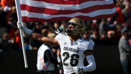 Colorado defensive back Isaiah Oliver carries the American flag onto the field. (Scott Olmos/USA Today Sports)