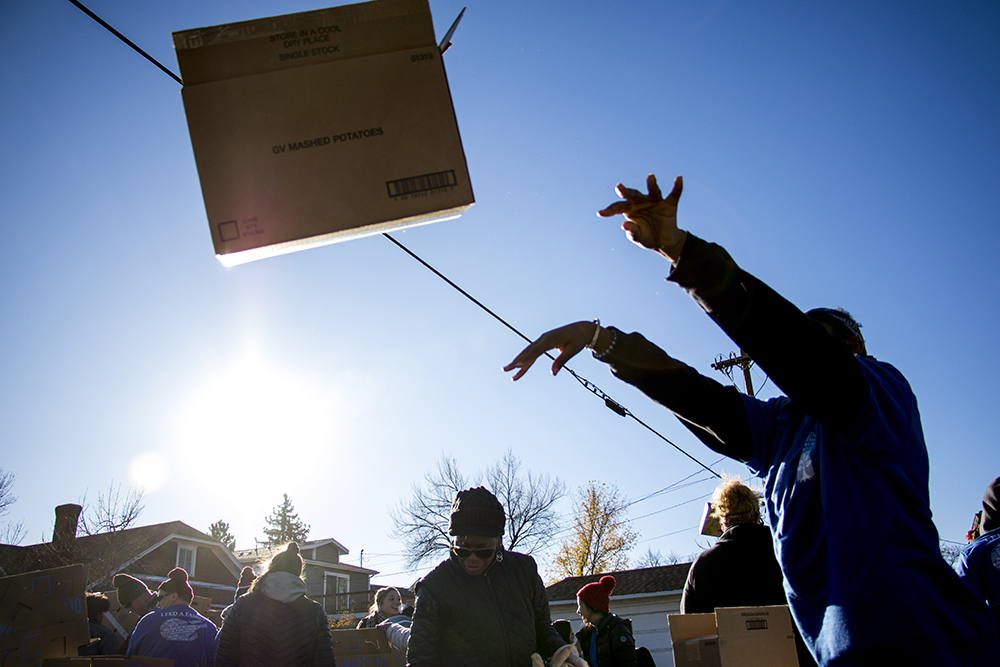 Emeral Palmer tosses an empty box. The Epworth Foundation's annual Feed a Family Thanksgiving dinner giveaway, Nov. 18, 2017. (Kevin J. Beaty/Denverite)  denver; colorado; denverite; kevinjbeaty; cole; thanksgiving; food pantry; food insecurity;